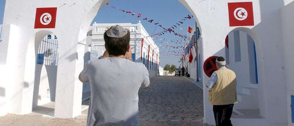 File picture shows an Israeli tourist taking a picture outside the synagogue of La Ghriba on the southern Tunisian island of Djerba on May 25, 2005 ( AFP Photo/Fethi Belaid )