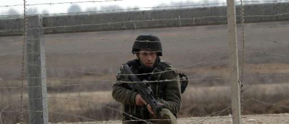 An Israeli soldier keeps watch next to the security fence standing on the Gaza border with Israel, east of Khan Yunis, in the southern Gaza Strip, on November 23, 2012 ( (AFP/File, Said Khatib) )
