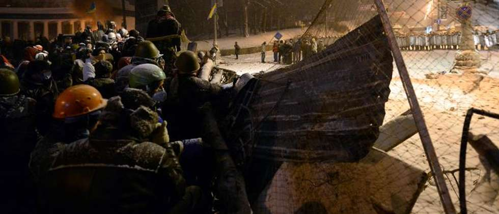 Ukrainian opposition activists stand next to a barricade during clashes with riot police in central Kiev early January 22, 2014