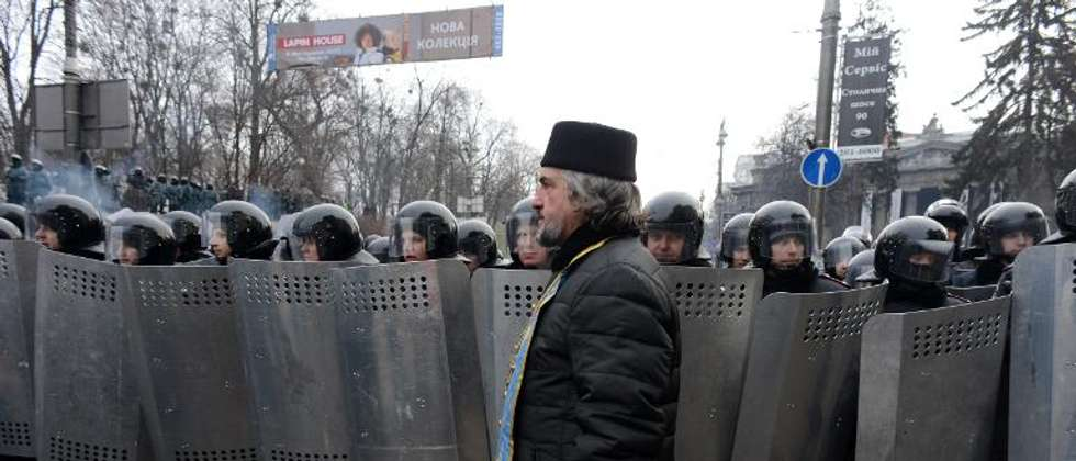 A Ukrainian priest walks past riot police after violent clashes in central Kiev, on January 21, 2014
