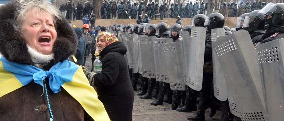 An Ukrainian opposition activist speak to riot-forces standing guard in front of the parliament in Kiev on January 21, 2014