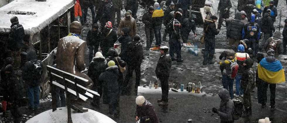 Ukrainian opposition activists stand next to burned police vehicles after violent clashes in Kiev on January 21, 2014