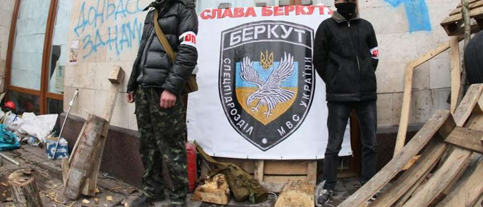 "Pro-Russia activists stand in front of a placard bearing the logo of Ukraine's disbanded elite Berkut riot police reading ""Glory to Berkut"" as they guard a barricade in the eastern Ukrainian city of Donetsk on April 14, 2014 ( Alexander Khudoteply (AFP) )"