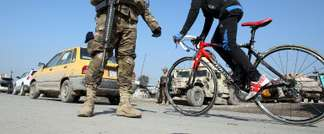 A boy cycles past Iraqi soldiers monitoring a checkpoint east of Baghdad on January 6, 2014 ( Ali Al-Saadi (AFP) )
