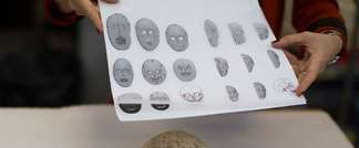 An Israel Museum Curator of prehistoric cultures and the Face to Face Exhibition shows diagrams of one of the rare 9,000-year-old Neolithic stone masks, all originating from the Judean Hills and Judean Desert, which are to go on public display for the fir ( AFP )