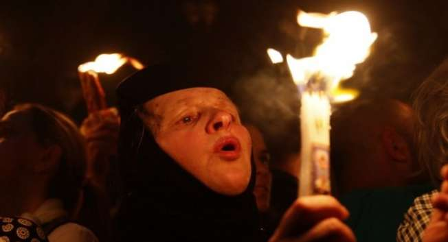 "A Christian Orthodox worshipper holds a candle lit from the ""Holy Fire"" as thousands gather in the Church of the Holy Sepulcher in Jerusalem's old city on April 19, 2014 ( Gali Tibbon/AFP )"