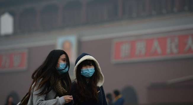 Two girls walk through a haze-shrouded Tiananmen Square in Beijing on February 23, 2014 ( AFP )