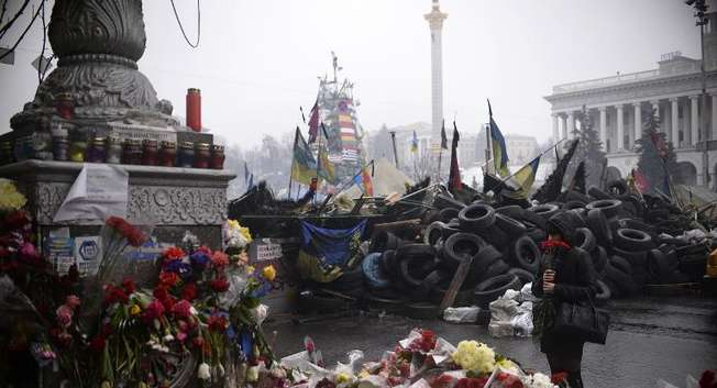 A woman holding red carnations mourns near a homage to victims of last month's clashes between anti-government protestors and riot police at a barricade on Independence Square in Kiev, on March 3, 2014 ( Dimitar Dilkoff (AFP) )