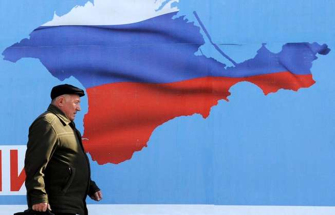 A man walks past a poster in Sevastopol on March 11, 2014 depicting Crimea in the colors of the Russian flag (Viktor Drachev (AFP))