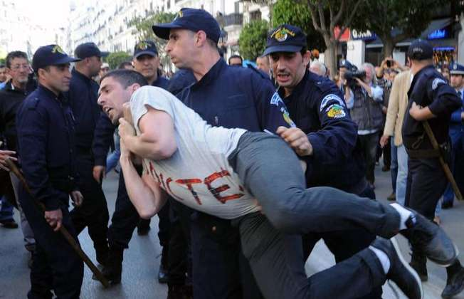 "Algerian police arrest a protestor from the Barakat movement (""That's enough""), as they demonstrate in Algiers on April 16, 2014 against President Bouteflika Abdelaziz running for a fourth term in presidential elections (Farouk Batiche (AFP))"