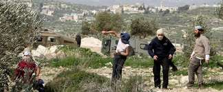 Masked Israeli settlers from the Havat Gilad settlement throw stones at Palestinian villagers near Farata, east of the West Bank ciy of Qalqilya, on February 28, 2012 (AFP)