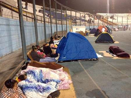 Locals take refuge at the city stadium following a tsunami alert after a powerful 8.2-magnitude earthquake hit off Chile's Pacific coast, on April 2, 2014 in Iquique ( Aldo Solimano (AFP) )