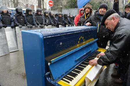 A man plays on a piano decorated as the EU flag in front of riot police as protesters picket Viktor Yanukovych's presidential office in Kiev on December 7, 2013 ( Sergei Supinsky (AFP) )