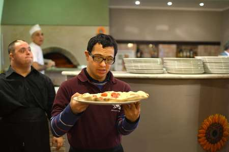 Alessandro Giusto (C), a young man with Down syndrome, serves a pizza at the Girasoli restaurant in Rome on January 28, 2014 ( Gabriel Bouys (AFP/File) )