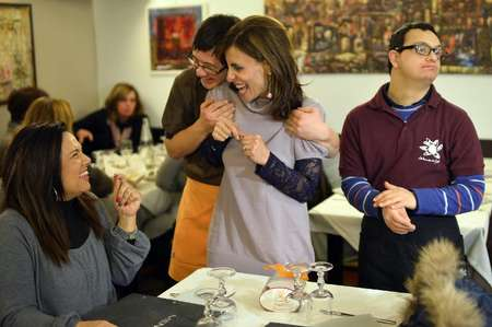 Simone Ippoliti (2nd L), a young waiter with Down syndrome, jokes with customers next to his colleague Alessandro Giusto (R) at the Girasoli restaurant in Rome on January 28, 2014 ( Gabriel Bouys (AFP/File) )