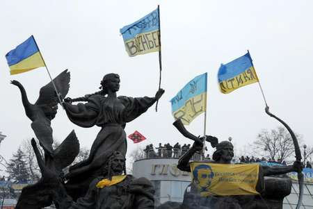 Flags are attached to a statue during an opposition rally at Independence Square in Kiev on December 7, 2013 ( Viktor Drachev (AFP) )